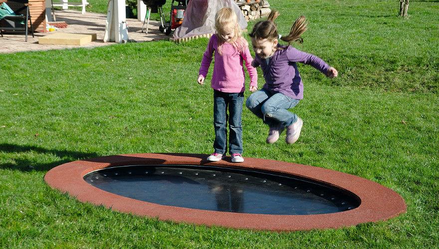 Ebenerdiges Trampolin auf einem Campingplatz mit spielenden Kindern