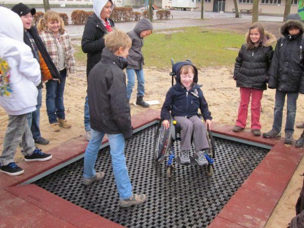 Junge mit Rollstohl auf ebenerdig eingegrabenen Trampolin 6m