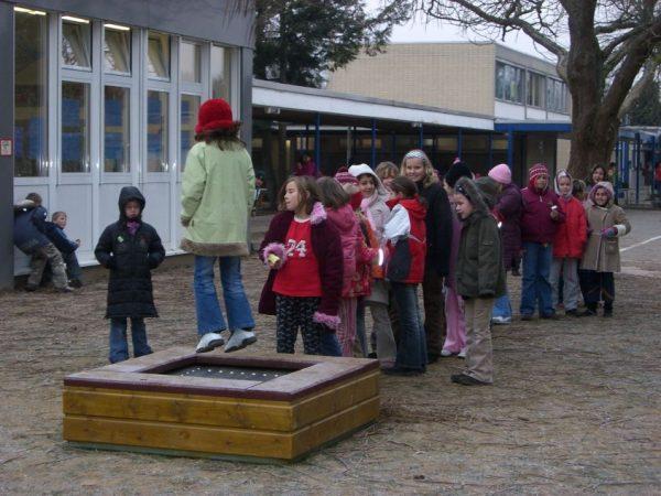 Kinder genießen das Springen auf einem Trampolin zum Eingraben Modell Piccolo auf einem Schulhof